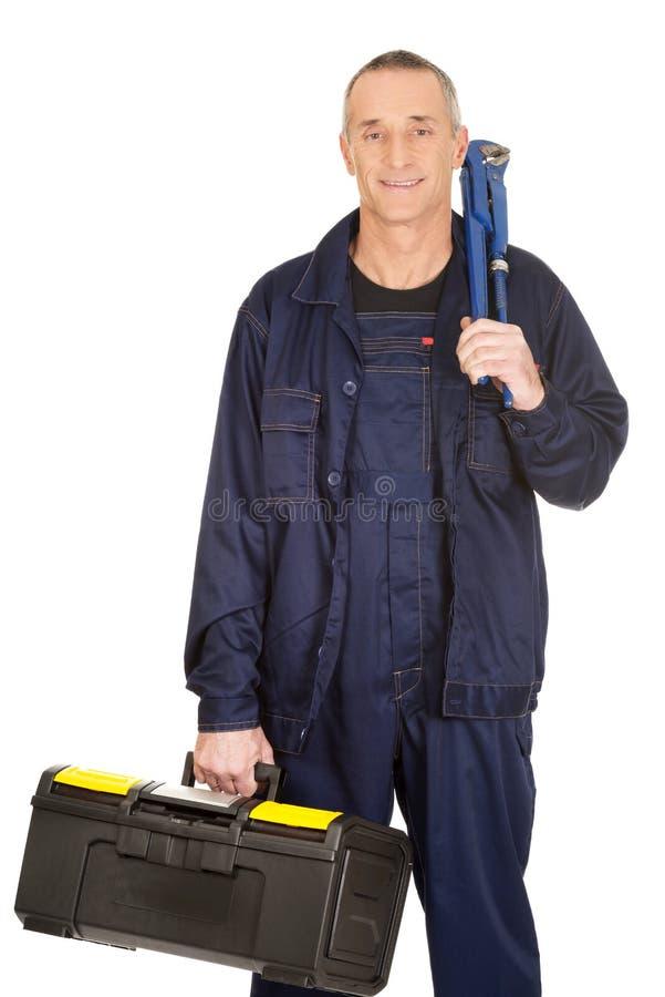 Travailleur mûr avec le sac et la clé d'outillages photos stock