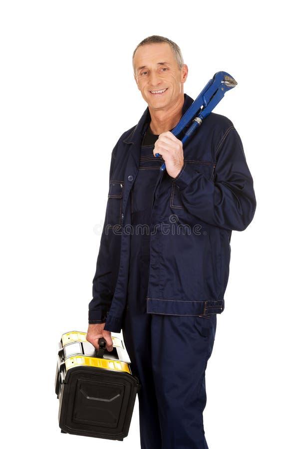 Travailleur mûr de sourire avec le sac et la clé d'outillages photo stock