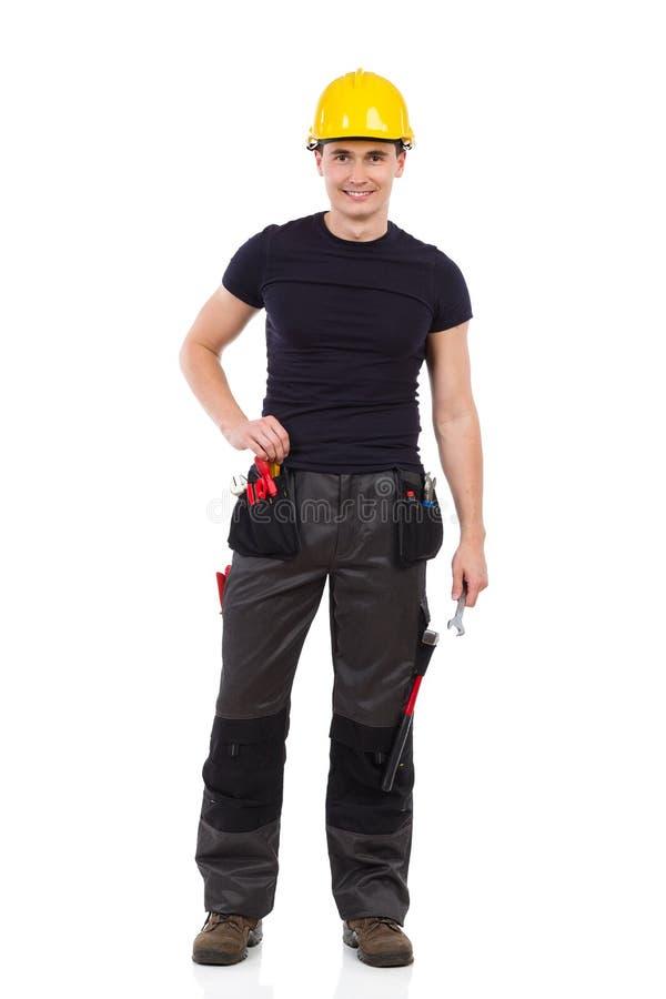 Travailleur manuel décontracté posant avec une clé photos stock