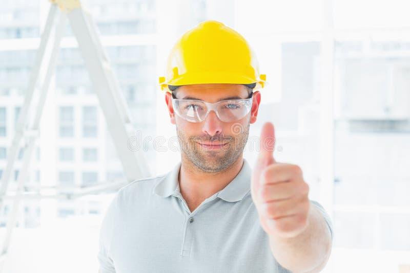 Travailleur manuel faisant des gestes des pouces au site photo stock