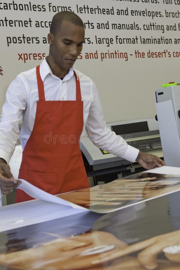 Travailleur manuel industriel travaillant dans la presse typographique image stock