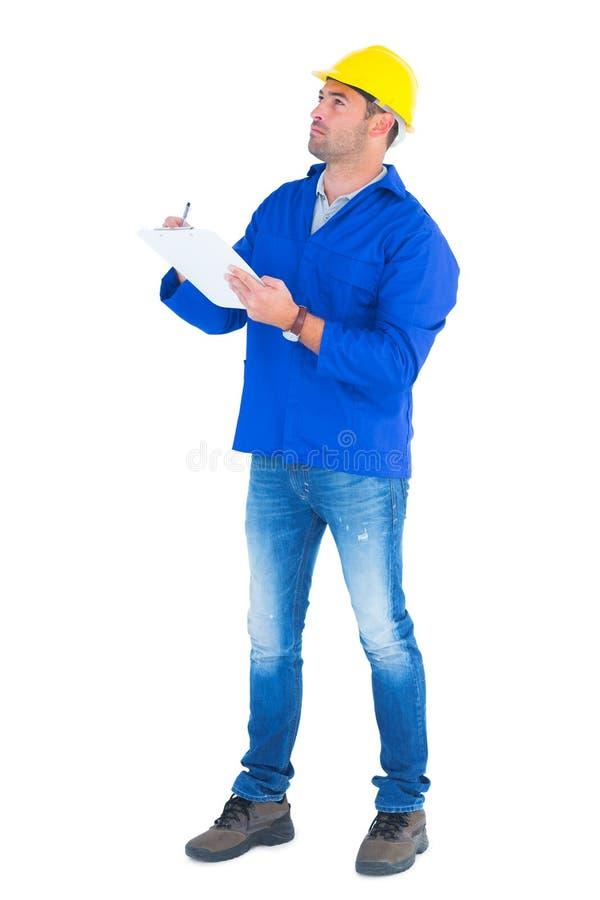 Travailleur manuel recherchant tout en écrivant sur le presse-papiers photographie stock