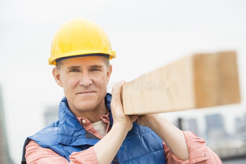 Travailleur manuel sûr portant la planche en bois photographie stock libre de droits