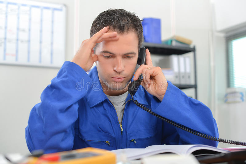 Travailleur manuel soumis à une contrainte au téléphone images libres de droits