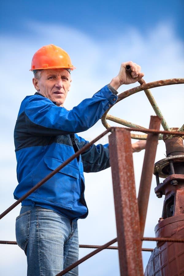 Travailleur manuel supérieur tournant la porte énorme de valve photos libres de droits