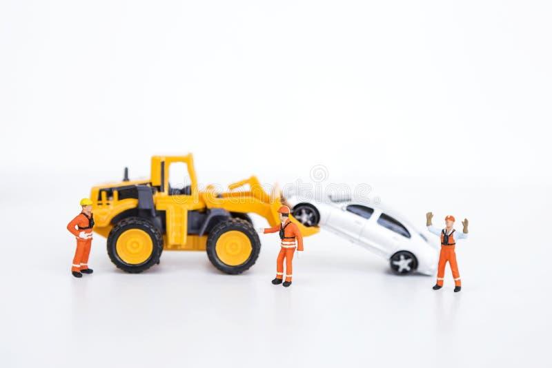 Travailleur miniature avec la voiture mobile de camion avant de chargeur photo libre de droits