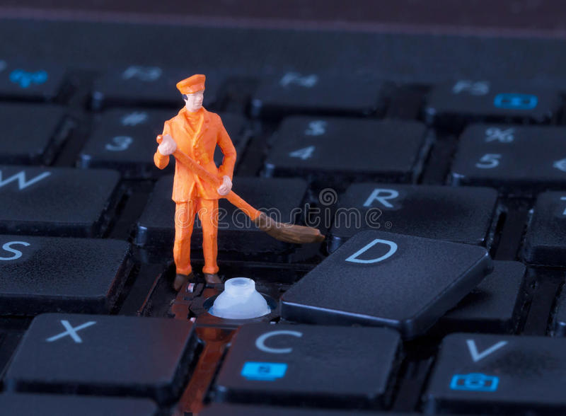 Travailleur miniature avec le balai travaillant au clavier photo libre de droits