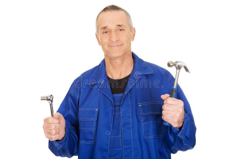 Travailleur montrant sa clé et marteau image libre de droits
