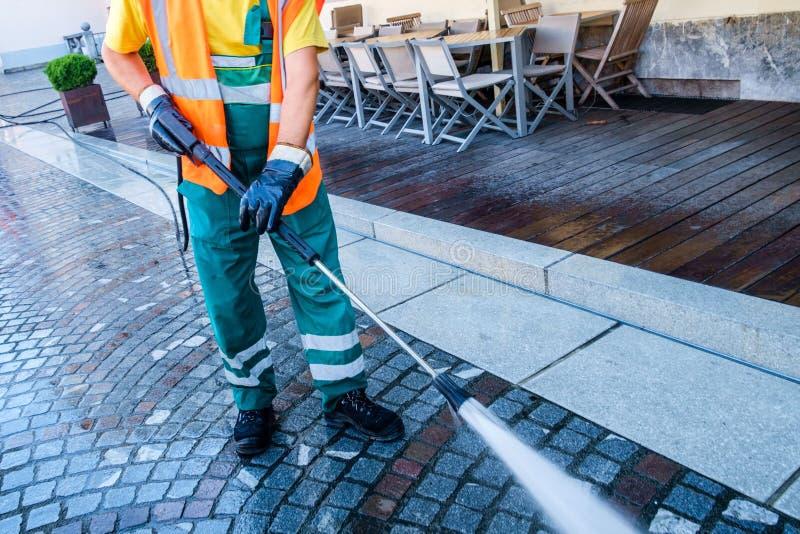 Travailleur nettoyant la rue pavée en cailloutis image libre de droits