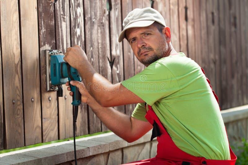 Travailleur polissant la vieille barrière en bois avec la machine-outil - une vibration image libre de droits