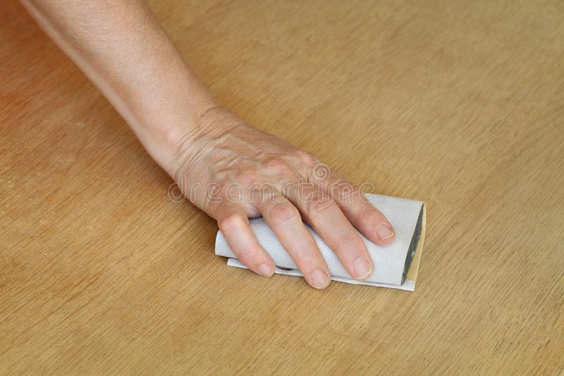Travailleur ponçant la planche en bois image stock