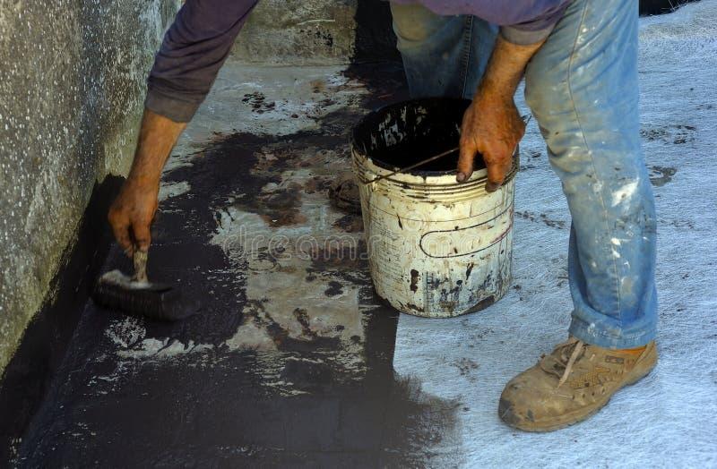 Travailleur posant avec le liquide bitumeux de gaine de brosse images stock
