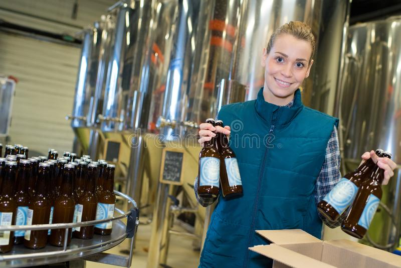 Travailleur positif dans des manteaux blancs sur l'usine de brasserie de bière photo stock