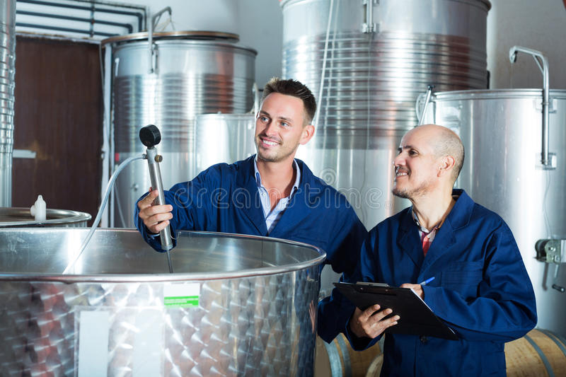 Travailleur prenant des notes dans la section de fermentation photo libre de droits