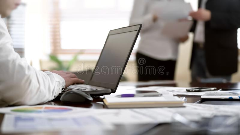 Travailleur prenant des notes sur l'ordinateur portable tandis que deux collègues discutant des papiers au bureau images stock