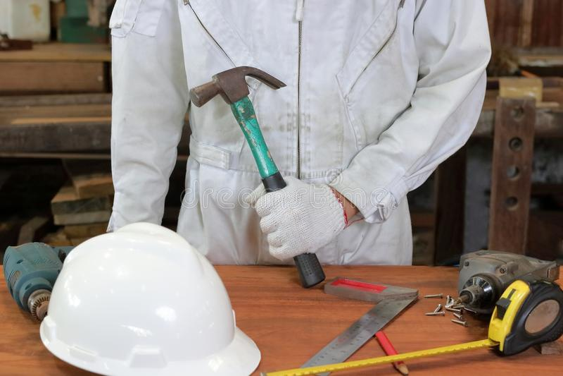 Travailleur professionnel avec le marteau se tenant uniforme de sécurité avec d'autres outils sur l'établi en bois dans l'atelier image stock