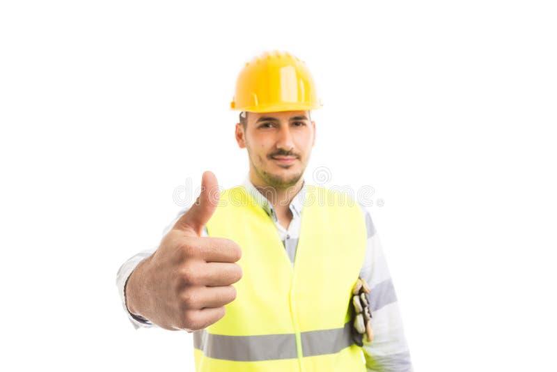 Travailleur professionnel beau et confindent montrant des ges de pouce- photos stock