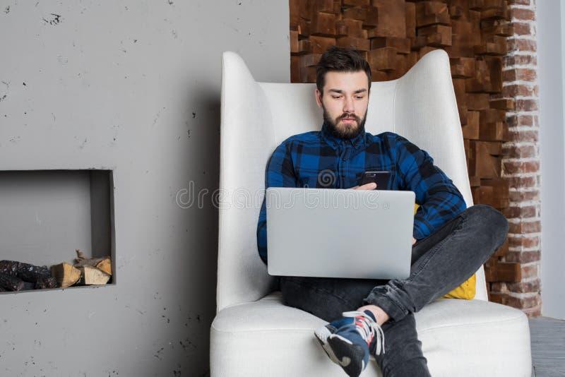 Travailleur qualifié d'Internet de distance de type élégant de hippie employant le téléphone portable et le filet-livre pour le t photographie stock libre de droits