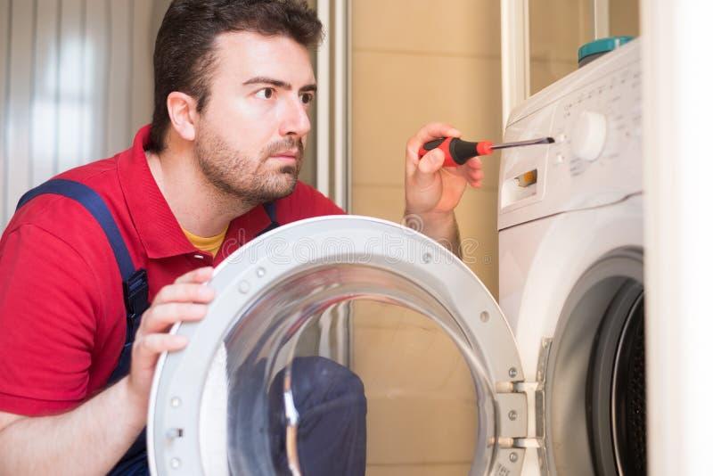 Travailleur réparant la machine à laver dans la salle de bains image stock