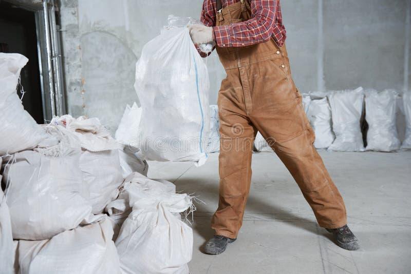 Travailleur rassemblant des déchets de construction dans le sac images stock