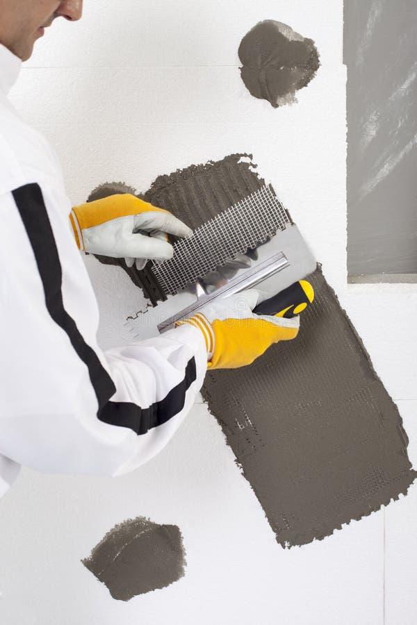 Travailleur renforçant un châssis de fenêtre photos stock