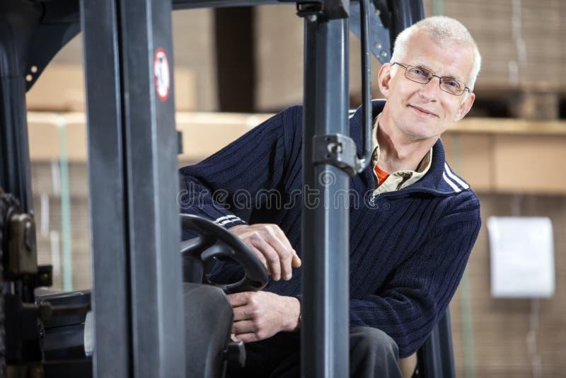 Travailleur sûr dans le chariot élévateur à l'entrepôt photos stock