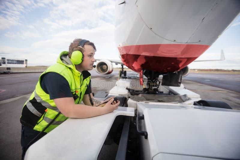 Travailleur se penchant sur le camion de remorquage avec l'avion sur la piste photo libre de droits