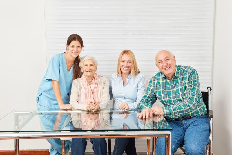 Travailleur social et famille heureuse dans la maison de retraite images libres de droits