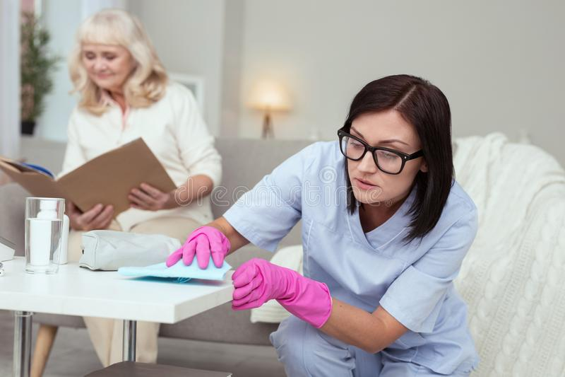Travailleur social féminin attentif rendant propre image stock