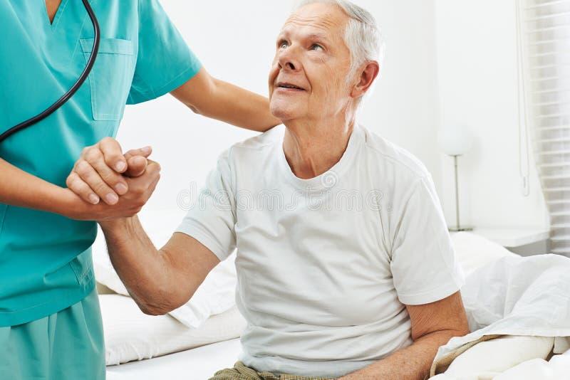 Travailleur social gériatrique aidant le vieil homme image stock