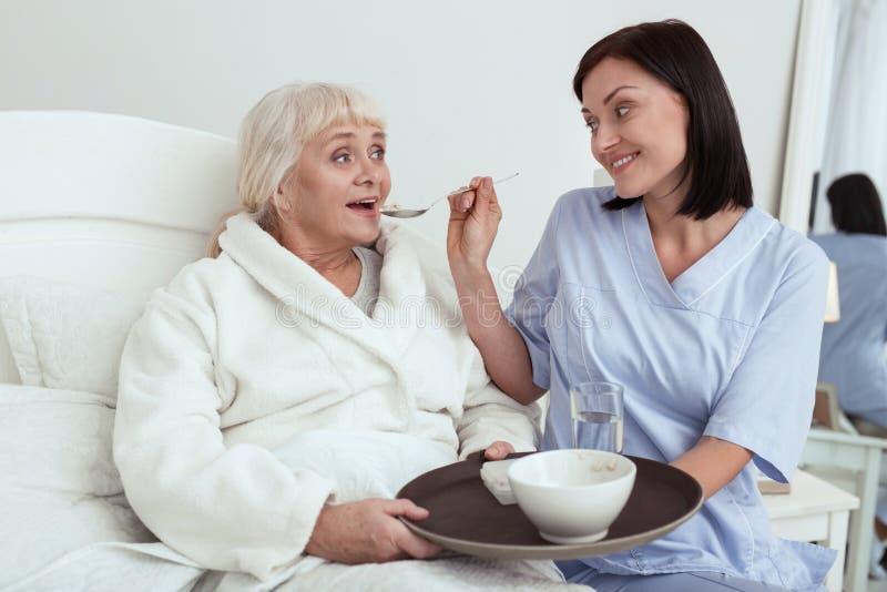 Travailleur social joyeux donnant le petit déjeuner à une femme plus âgée photographie stock