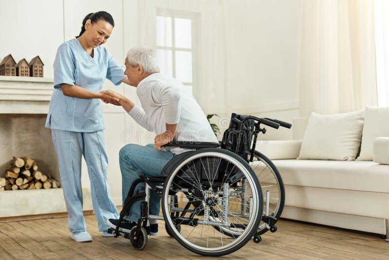 Travailleur social utile joyeux tenant sa main de patients images stock