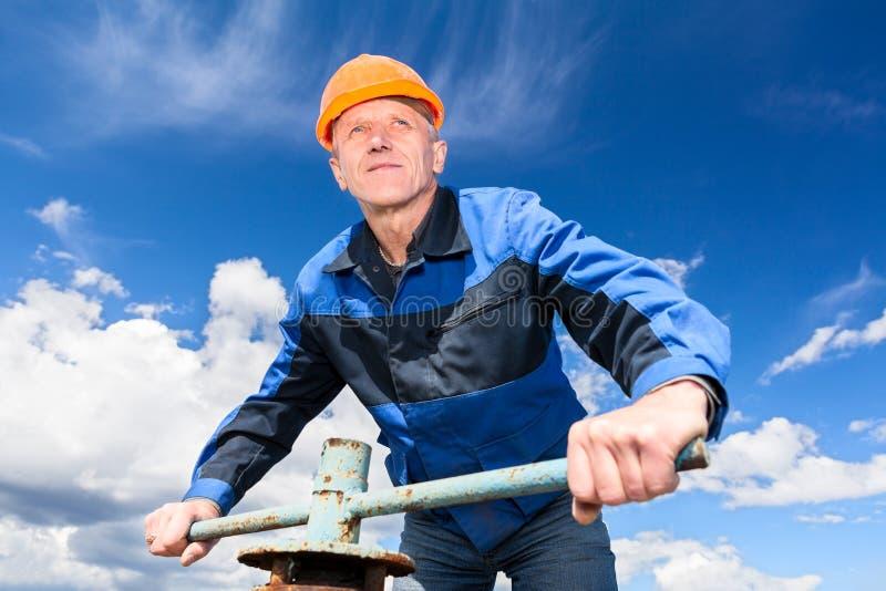 Travailleur supérieur contre le ciel bleu photo stock