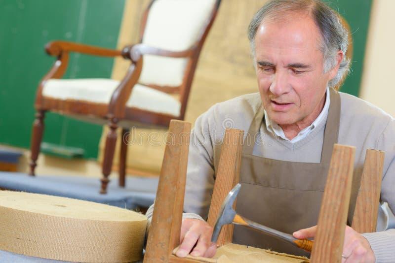 Travailleur supérieur heureux de portrait s'asseyant dans l'atelier photos stock