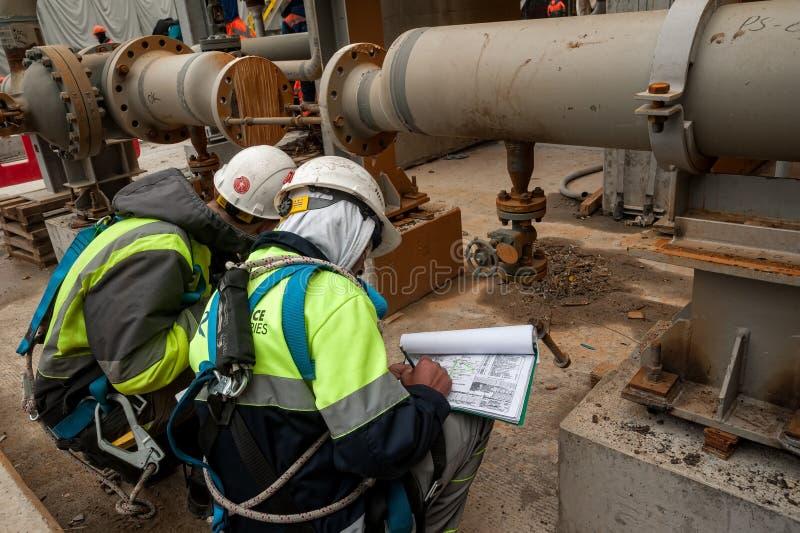 Travailleur sur des documents d'un contrôle de chantier de construction images libres de droits