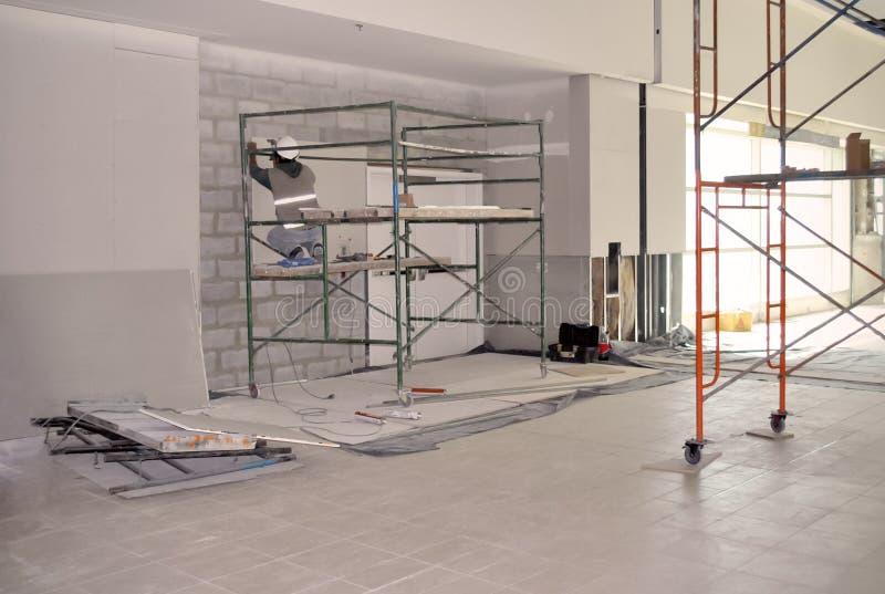 Travailleur sur l'échafaudage installant le mur de gypse photographie stock libre de droits
