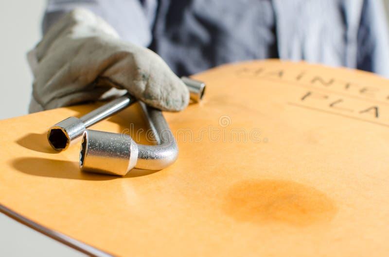 Travailleur tenant un dossier de plan et d'outils d'entretien photos stock