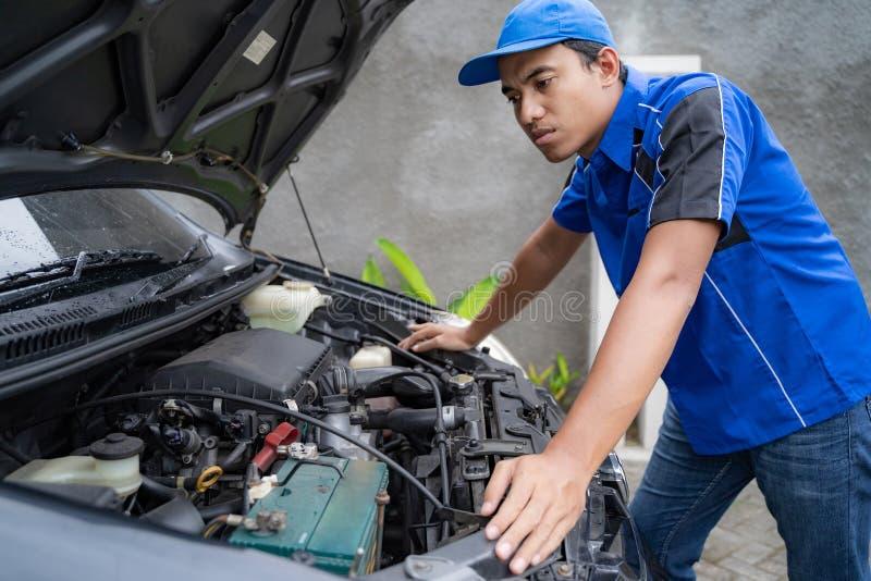 Travailleur uniforme bleu d'ing?nieur de voiture regardant dans le moteur de voiture photo libre de droits