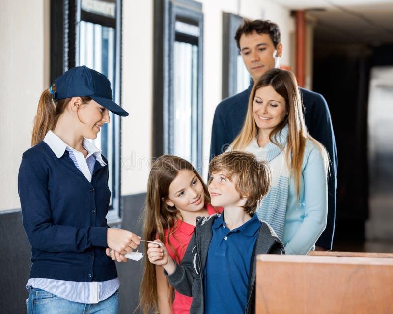 Travailleur vérifiant des billets de famille au cinéma photo stock