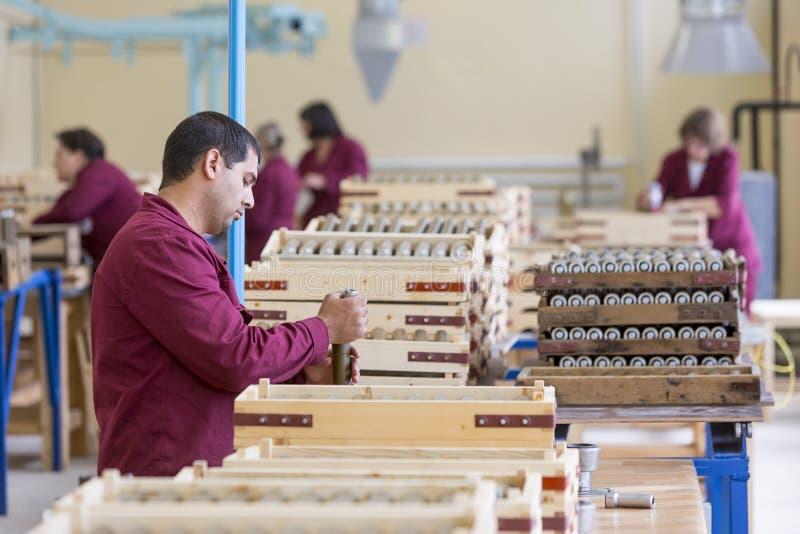 Travailleur vérifiant des explosifs de RPG dans l'usine de munitions image libre de droits
