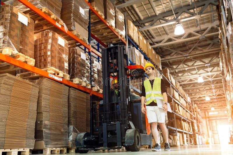 Travailleurs à l'aide du chariot élévateur de technologie dans l'entrepôt photographie stock