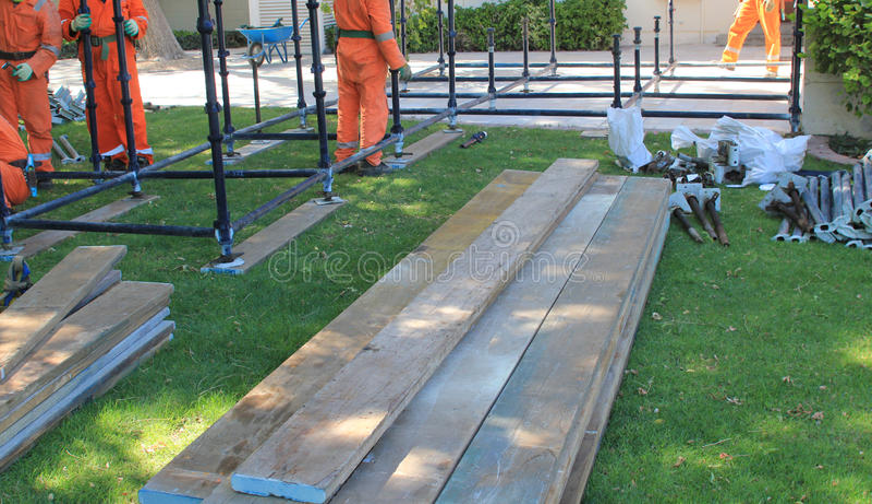 Travailleurs érigeant l'échafaudage avec des poteaux et des planches photographie stock libre de droits