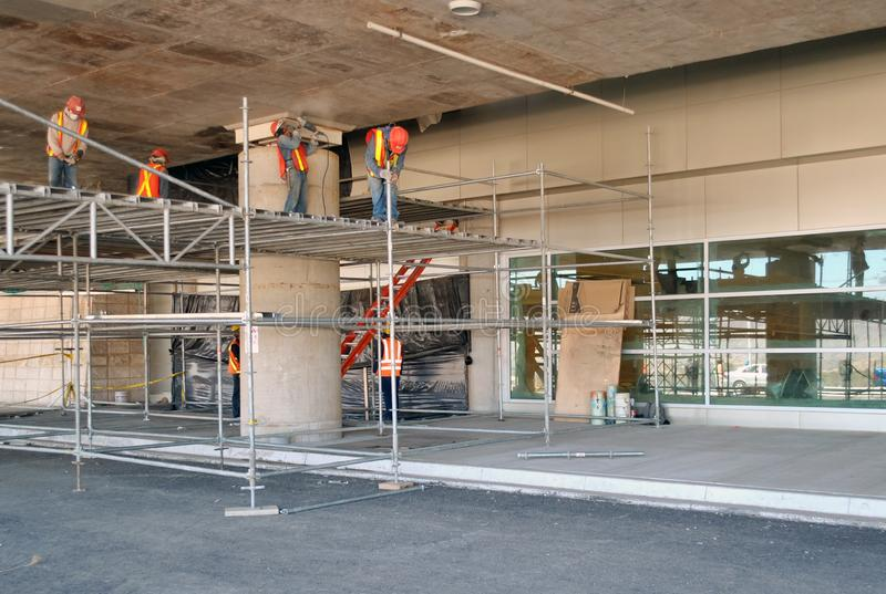 Travailleurs assemblant l'?chafaudage dans un parking en construction images stock