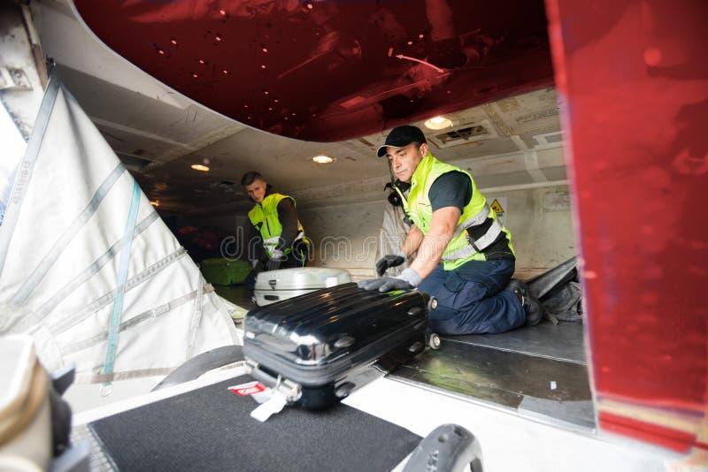 Travailleurs chargeant le bagage dans l'avion image stock