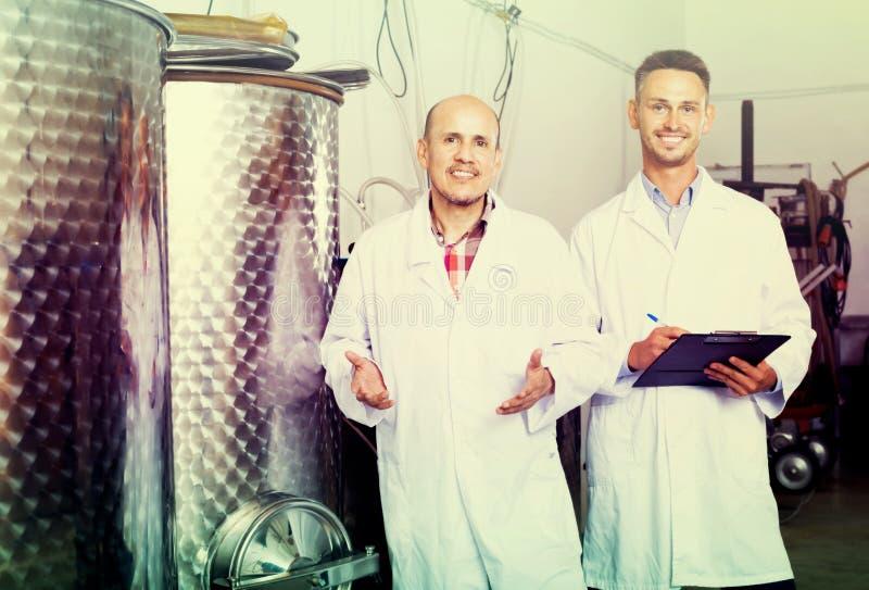 Travailleurs d'établissement vinicole se tenant dans la section de fermentation photo libre de droits