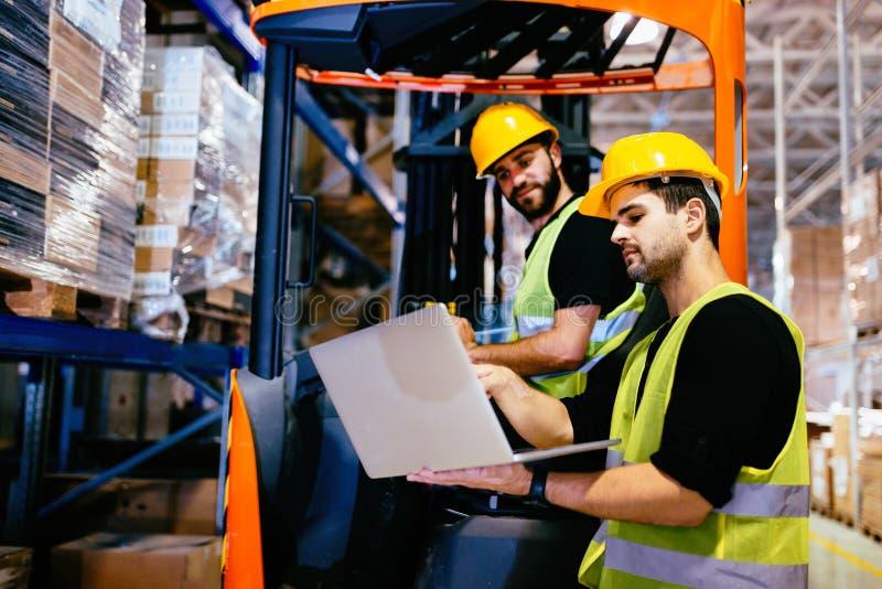 Travailleurs d'entrepôt collaborant avec le chargeur de chariot élévateur images stock