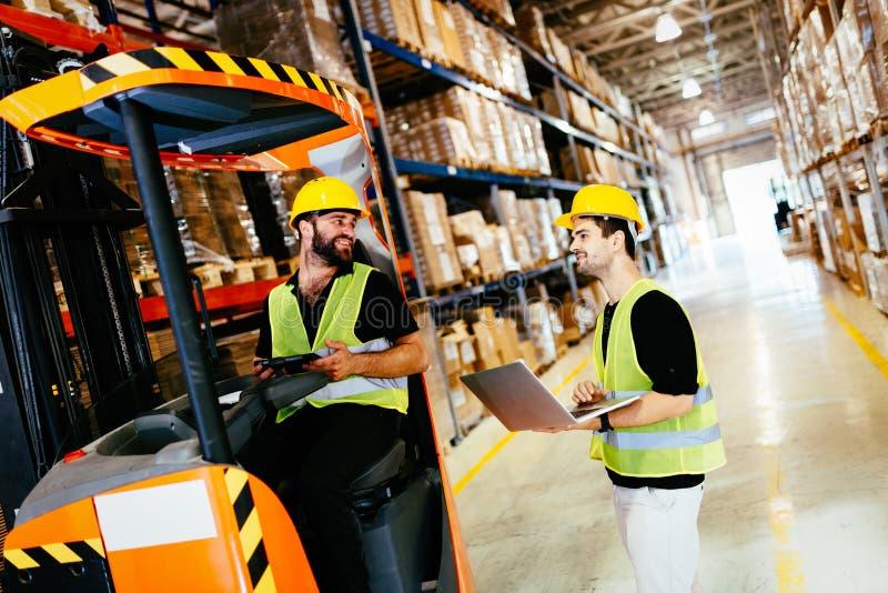 Travailleurs d'entrepôt collaborant avec le chargeur de chariot élévateur photos libres de droits