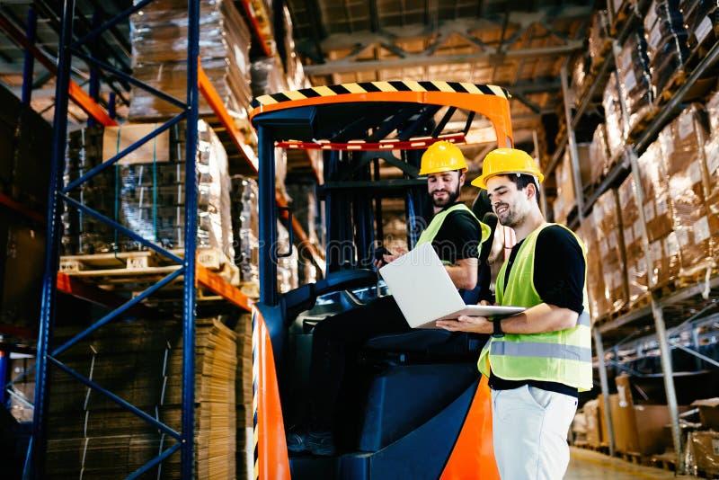 Travailleurs d'entrepôt collaborant avec le chargeur de chariot élévateur photographie stock