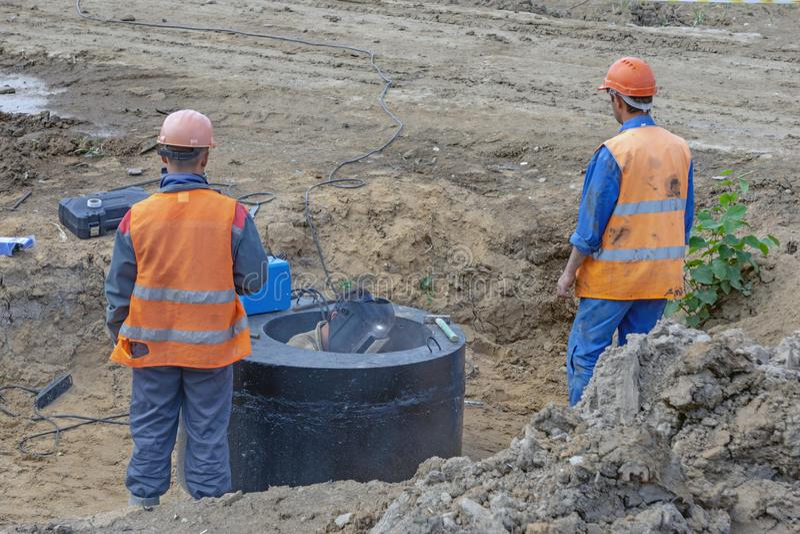 Travailleurs dans l'uniforme orange au chantier de construction photo libre de droits
