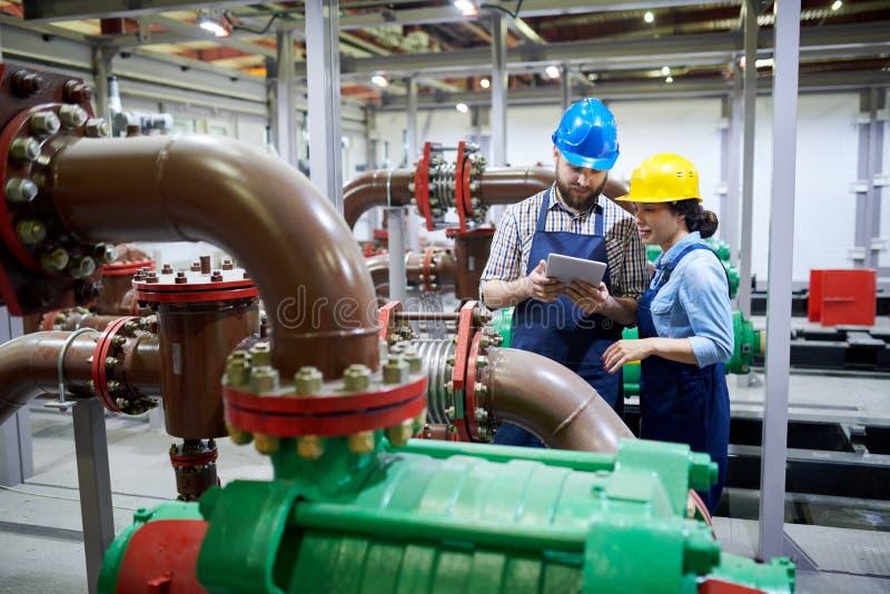 Travailleurs dans le système de purification photos stock